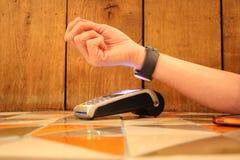 Pdq sans contact de smartwatch de paiement avec la main tenant la carte de crédit pour payer Photos libres de droits