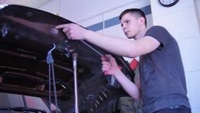 Pdr Retrait de r?paration de bosselure de Paintless Un jeune type étend une bosselure avec un crochet en acier sans peinture selo banque de vidéos