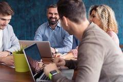 Pełna koncentracja przy pracą Grupa młodzi ludzie biznesu pracuje i komunikuje podczas gdy siedzący przy biurowym biurkiem fotografia royalty free