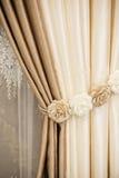 Peça da cortina belamente drapejada na janela na sala Tieback floral Feche acima da cortina empilhada Cu luxuoso bege e marrom imagem de stock