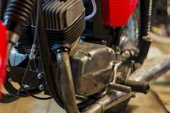 A peça da motocicleta vermelha do vintage estacionou na garagem, close-up fotos de stock royalty free