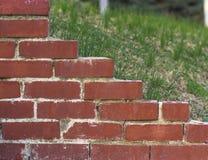 Peça da parede do tijolo vermelho no fundo do gramado verde fotografia de stock