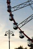 Peça da roda de ferris com cabines e do poste de luz no fundo do céu do por do sol Imagens de Stock