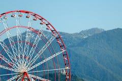 Peça da roda de Ferris contra o contexto das montanhas cobertas com as florestas Imagem de Stock Royalty Free