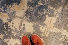 Peça das sapatilhas vermelhas na superfície do assoalho velho do emplastro fotografia de stock