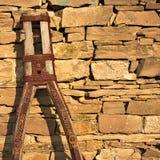 Peça de um vagão velho da exploração agrícola e de uma parede de pedra antiga Fotografia de Stock Royalty Free