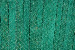 Peça de uma cerca de madeira coberta com a malha do ferro Foto de Stock