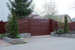 Peça de uma cerca de madeira marrom e de umas portas fechados com as árvores coníferas decorativas na rua imagem de stock royalty free