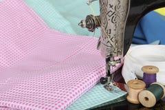 Peça de uma máquina de costura velha com uma pata, uma agulha, uns carretéis retros da linha e umas partes de tela colorida Fundo Imagens de Stock Royalty Free