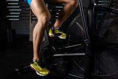 A peça do close-up da vista lateral do homem novo nos esportes calça o ciclismo no gym imagem de stock royalty free