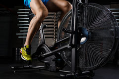 A peça do close-up da vista lateral do homem novo nos esportes calça o ciclismo no gym Imagens de Stock