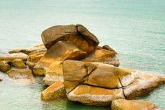 Peça do cume da montanha alga castigado pelo mau tempo das pedras da praia da grande coberta com as plantas e os escudos marinhos foto de stock royalty free