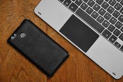 Peça do teclado e do smartphone do portátil no fundo de madeira imagens de stock