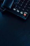 Peça do telefone em uma mesa de escritório preta Fotos de Stock Royalty Free