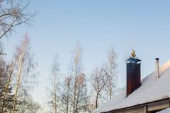 Peça do telhado coberto de neve da casa com a peça do telhado coberto de neve da casa com a chaminé de qual lá de qual lá é fumo imagem de stock