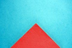 Peça do triângulo do guardanapo de papel vermelho no fundo azul do cartão, espaço da cópia, vista superior fotografia de stock royalty free