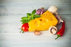 Peça o queijo com vegetais e a manjericão na placa de madeira Imagem de Stock Royalty Free