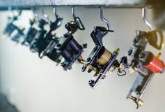 Peças da máquina da tatuagem da tinta da bobina, pendurando na prateleira de madeira, clos foto de stock