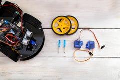 Peças da robótica Servo, chave de fenda que encontra-se em uma tabela de madeira Vista Foto de Stock