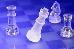 Peças do jogo de xadrez de vidro na luz azul Foto de Stock