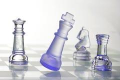 Peças do jogo de xadrez de vidro na luz azul Fotos de Stock