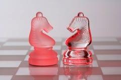 Peças do jogo de xadrez de vidro na luz vermelha Imagens de Stock Royalty Free