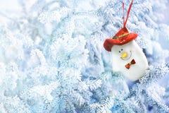 Peúga do boneco de neve do Natal que pendura em um ramo de árvore da neve Fotos de Stock