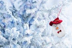 Peúga do boneco de neve do Natal que pendura em um ramo de árvore da neve Imagem de Stock Royalty Free
