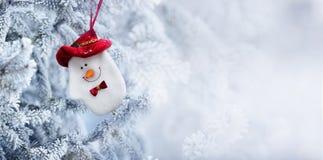 Peúga do boneco de neve do Natal que pendura em um ramo de árvore da neve Fotos de Stock Royalty Free