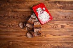 peúga feita malha Multi-colorida do bebê e uma caixa do metal com a imagem de Santa Claus em um fundo de madeira imagens de stock royalty free