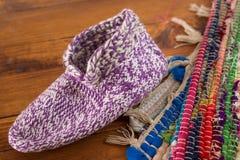 Peúga feito a mão de lãs e tapete colorido no fundo de madeira Foto de Stock