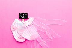 Peúgas cor-de-rosa e brancas do bebê - com laço no fundo cor-de-rosa com ele ` s um sinal do quadro-negro da menina fotografia de stock