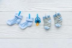 Peúgas do bebê na corda no fundo de madeira Imagens de Stock Royalty Free