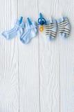 Peúgas do bebê na corda no fundo de madeira Fotografia de Stock