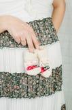 Peúgas do bebê nas mãos da mulher gravida Foto de Stock
