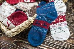 Peúgas do Natal e cesta de lavanderia multi-coloridas dispersadas Foto de Stock Royalty Free