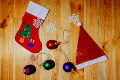 Peúgas do Natal e chapéu de Santa com flocos de neve das bolas Foto de Stock