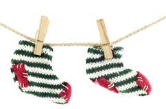 Peúgas do Natal que penduram na linha de roupa Foto de Stock