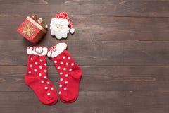 Peúgas e decoração vermelhas do dia de Natal no backgrou de madeira Imagens de Stock Royalty Free