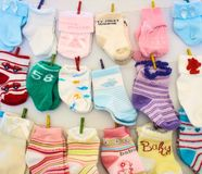 Peúgas e mitenes do bebê que penduram em linhas com os Pegs de roupa diminutos fotografia de stock