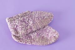 Peúgas feitos a mão de lãs no fundo violeta Foto de Stock Royalty Free