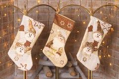 Peúgas que penduram sobre a chaminé para presentes de Santa Claus Foto de Stock Royalty Free