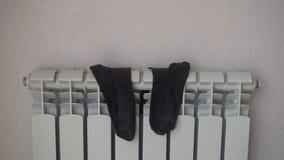 Peúgas, secando no radiador do aquecimento após o lavagem video estoque