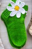 Peúgas verdes feitos a mão de lãs com a flor branca Fotos de Stock Royalty Free