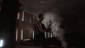 Pełen wdzięku baleriny dancingowi baletniczy elementy w zmroku z światłem i dymem na tle, zwolnione tempo zdjęcie wideo