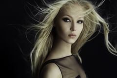 Pełen wdzięku blondynki dziewczyna w doskonalić uzupełnia z włosy rozpraszającym wiatrem, odosobnionym na czarnym tle zdjęcia royalty free