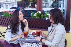 Pełen wdzięku dziewczyny śmia się herbaty i pije Zdjęcie Stock