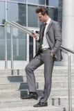Pełna długość biznesmena wysylanie sms przez telefonu komórkowego podczas gdy stojący na krokach na zewnątrz biura Fotografia Royalty Free