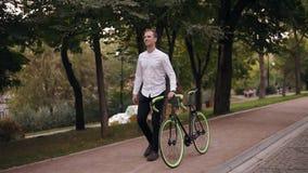 Pełna długość caucasian uśmiechnięty młody człowiek w białym koszulowym odprowadzeniu z bicyklem na ulicie w miasteczku Staczać s zbiory