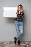 Pełna długość dosyć ono uśmiecha się kobiety mienia pustego miejsca deska fotografia royalty free